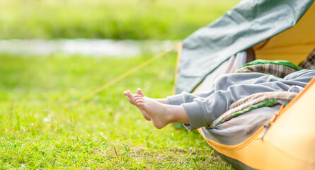 Little girl enjoys the rest, sticking her legs out of the tent in nature. Empty space for text