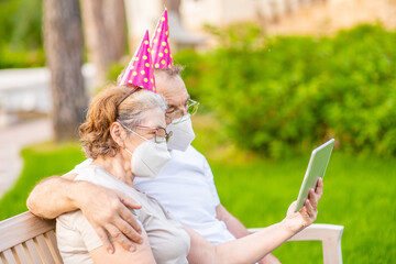 Elderly people wearing party's caps and protective face masks celebrates  birthday with her family on video call during the coronavirus epidemic