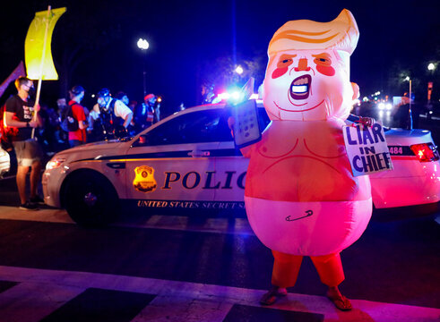 An inflatable costume depicting U.S. President Donald Trump as a baby is pictured during a protest as security officers block the path on Constitution Avenue in Washington