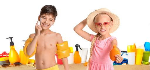 Little children with sun protection cream and beach accessories on white background