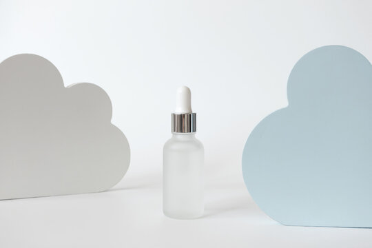 Hydrating moisture mist glass bottle with dropper, cloud shape decor on white background. Minimalist composition beauty product presentation. Concept delicate skin care