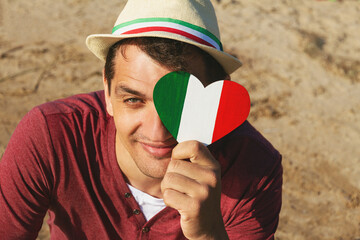 young smiling man in red t-shirt and hat and wooden heart with italy flag
