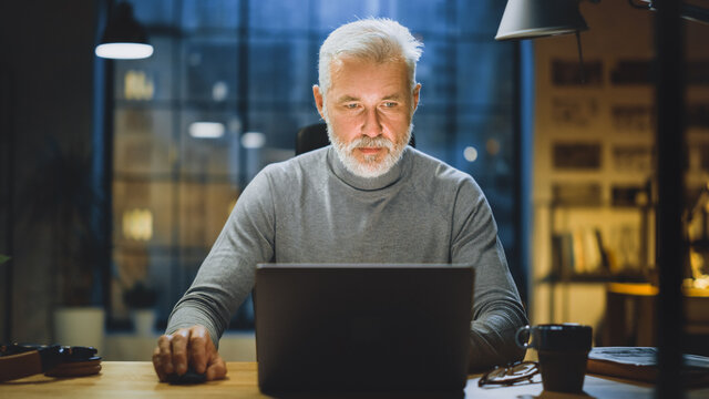 Portrait of the Handsome and Successful Middle Aged Bearded Businessman Working at His Desk Using Laptop Computer. Working from Cozy Home Office / Studio with Window View of the City at Night