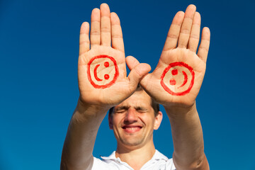 mens hand with paint red face and smile against blue sky, copy space, close up