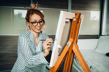 Beautiful artist woman painting in her room.