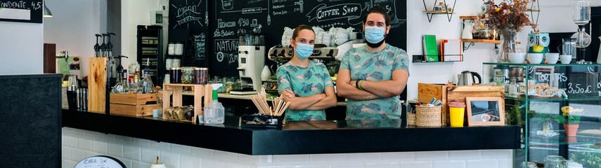 Coffee shop owners posing with masks according to the new normal