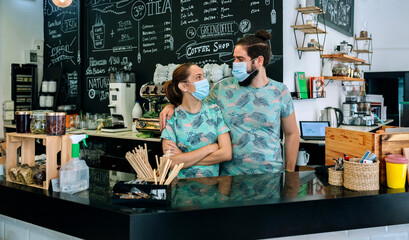 Coffee shop owners posing with masks looking to each other