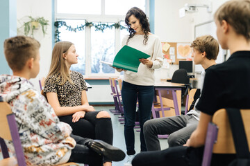 Group of teenagers sitting in a circle in front of them facing the nurse with a green notebook