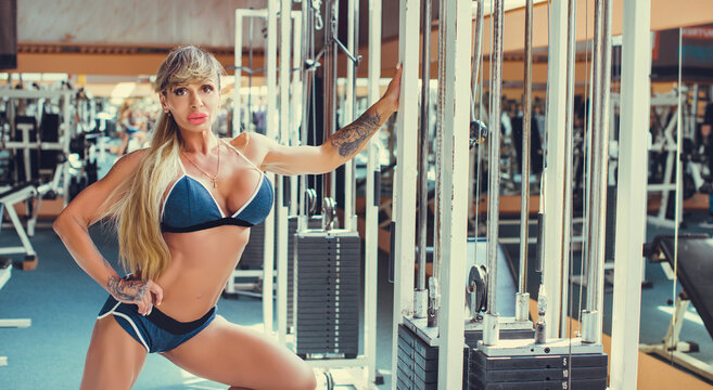 Bodybuilder mature sexy woman working out in a gym. Fitness woman, trained female body, lifestyle portrait, american middle age model