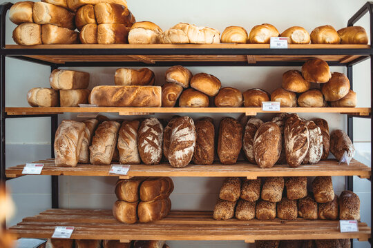 Fresh bread on shelves in bakery. Delicious loaves of bread in a german baker shop. Different types of bread loaves on bakery shelves. Modern bakery with assortment of bread