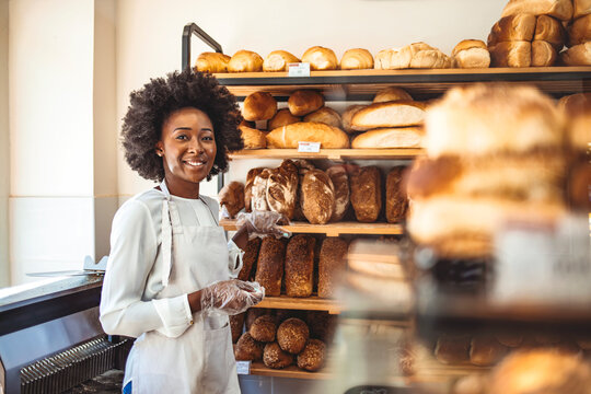 Attractive cheerful female baker smiling to the camera standing near the showcase copyspace. Female baker or saleswoman in her bakery selling fresh bread, pastries and bakery products in basket
