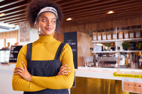 Female African coffee shop owner wearing face mask