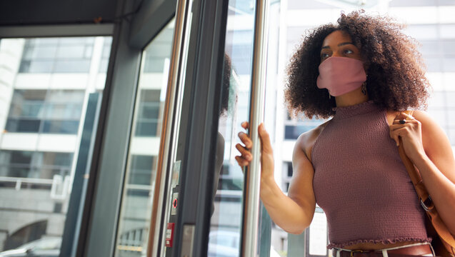 Young adult woman entering office wearing face mask