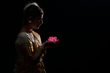 Mohiniattam artist smiling at a lotus flower in her hand