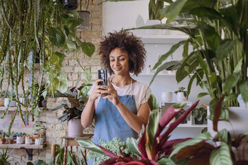 Small business Store Owner using smartphone photographing plants for promotion