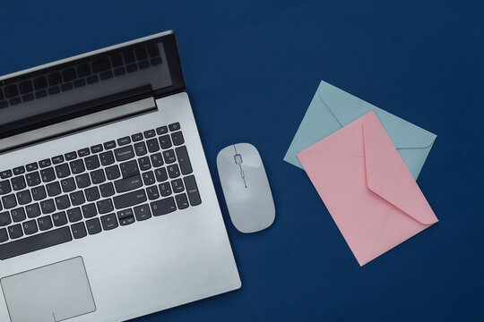 Laptop with pc mouse, envelopes on classic blue background. Color 2020. Top view.