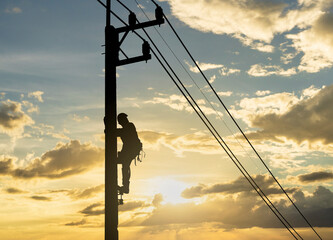 Obraz Silhouette man works with electricity on a pole with the sunset in the sky. - fototapety do salonu