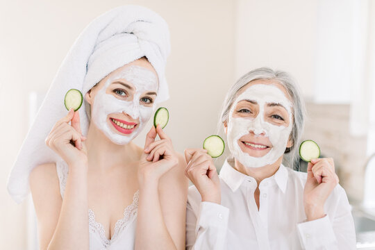 Morning skin care routine, family spa day. Pretty senior gray haired woman and her young attractive granddaughter making clay facial masks and posing to camera in kitchen with cucumber slices