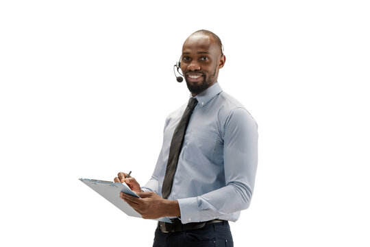 Works with gadgets and papers. Young african-american call center consultant with headset on white studio background. Copyspace for ad, text. Concept of professional occupation, work, job