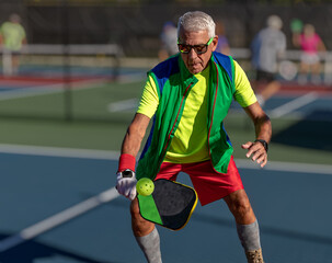 Senior man hitting a pickleball with paddle