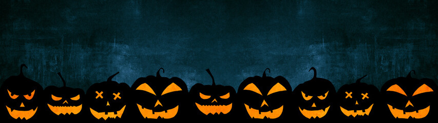 HALLOWEEN background banner wide panoramic panorama template -Silhouette of scary carved luminous cartoon pumpkins in the dark black blue night