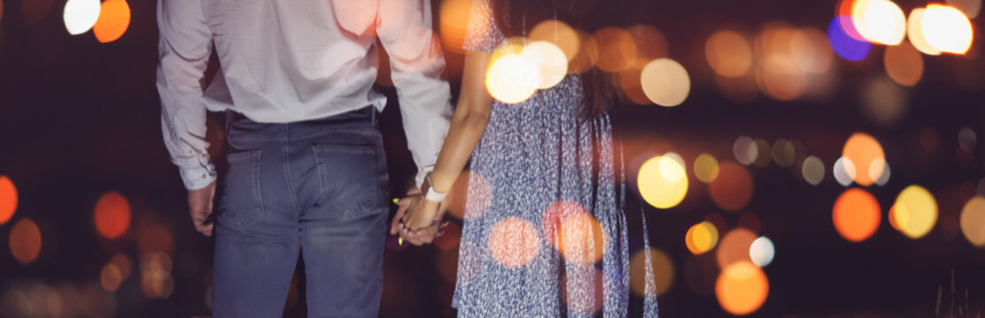 Romantic couple in love holds hands against backdrop of night city lights