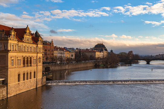 Beautiful view of Vltava river side with Bedřich Smetana Museum, National Theatre and Legion Bridge from Charles Bridge on sunny winter day with blue sky cloud, Prague,  Czech Republic