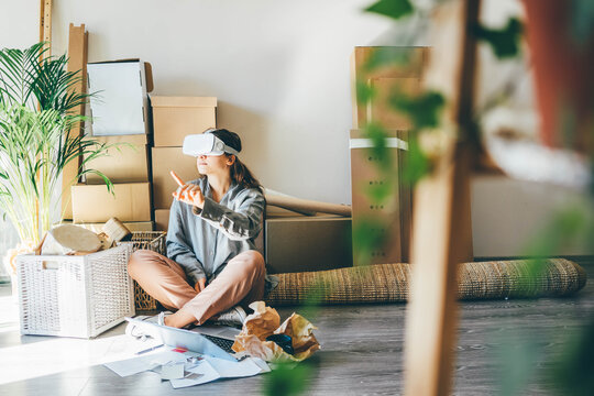 Girl in white VR headset looking at virtual object sitting against boxes in new flat.