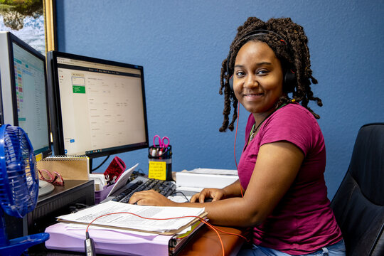 A portrait of an African American woman at her call center desk and her headset on, working from home, looking into camera smiling.