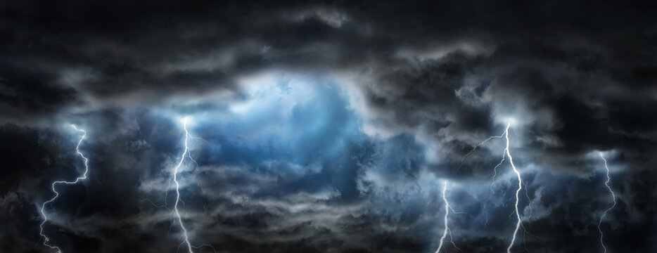 Sun rays, clouds and sparkling lightning in the dark sky. Thunderous dark sky with black clouds. Concept on the theme of weather, natural disasters, storm,  thunderstorms,, lightning.