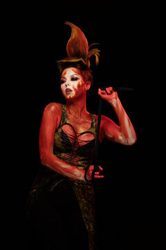 Young woman dancing in the fantasy  image of Flames and Fire in a red body art emotionally posing on a black background