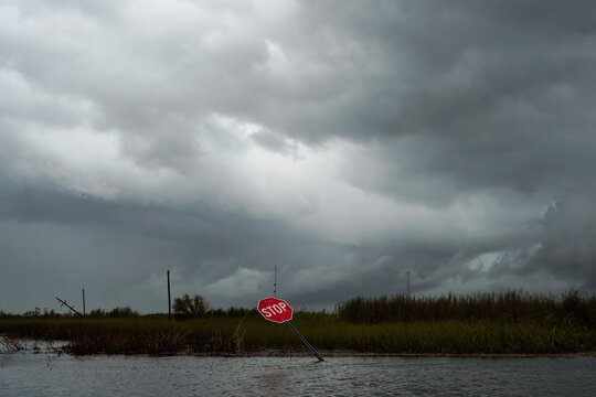 A damaged stop sign and flooding is seen after Hurricane Laura passed through the area in Creole