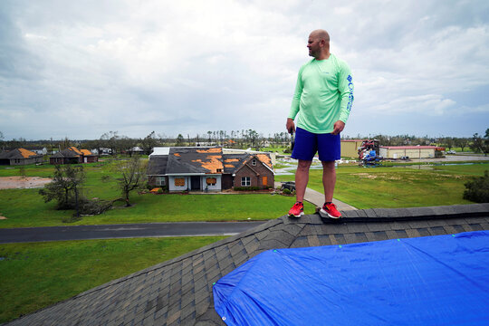 Corey Manual stands on the roof of neighbor Derek Kingham while helping patching damage to roof after Hurricane Laura passed through the area in Cameron Parish