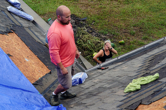 Jade Kingham looks up at her husband Derek on the roof of their home after Hurricane Laura passed through the area in Cameron Parish