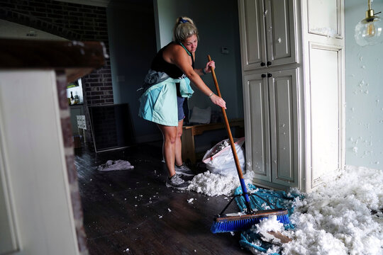 Jade Kingham cleans up ceiling insulation from her kitchen floor after Hurricane Laura passed through the area in Cameron Parish