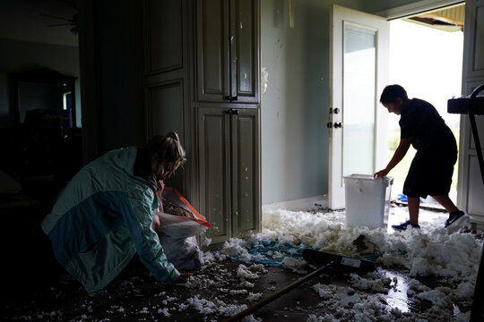 Jade Kingham and her son Lane clean up ceiling insulation from their kitchen floor after Hurricane Laura passed through the area in Cameron Parish