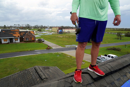 Damage to a home is seen behind Corey Manual as he stands on the roof of neighbor Derek Kingham while helping patch damage to the roof after Hurricane Laura passed through the area in Cameron Parish
