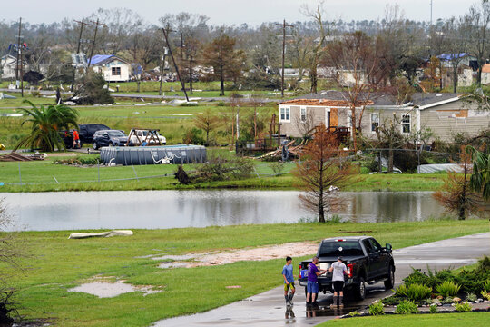 People unload items from a truck as damage is seen to homes after Hurricane Laura passed through the area in Cameron Parish