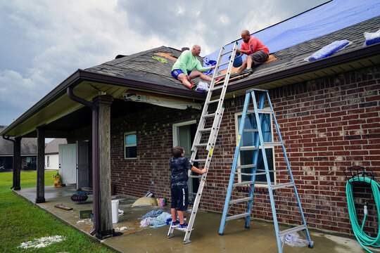 Lane Kingham stands on a ladder as his father Derek gets help from neighbor Corey Manual while patching damage to his roof after Hurricane Laura passed through the area in Cameron Parish