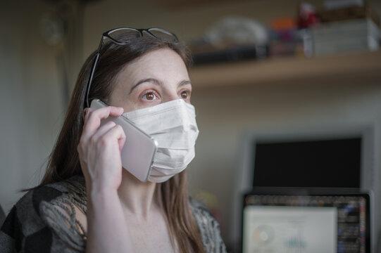 Joven mujer blanca con gafas sobre la cabeza lleva puesta una mascarilla higiénica antivirus mientras habla por teléfono móvil mostrando sus emociones.