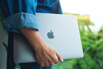 Aug 18th 2020 : A woman holding an Apple MacBook Pro laptop computer to go to somewhere , Chiang mai Thailand