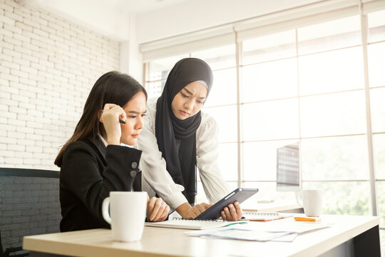 multiethnic asian female muslim workers working in office as team using tablet device to strategize and planning work concept of diversity of culture different race type of people co-working together