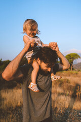 Child daughter sitting on father shoulders walking outdoor family playing together having fun authentic lifestyle happy emotions