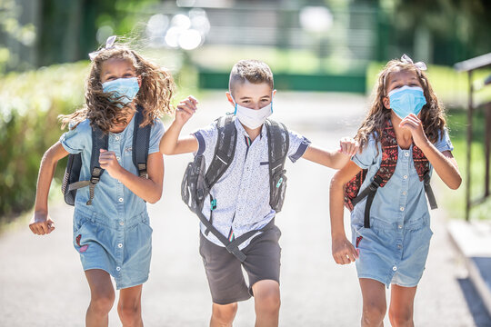 Happy schoolchildren with face masks run from the joy of returning to school during the Covid-19 quarantine