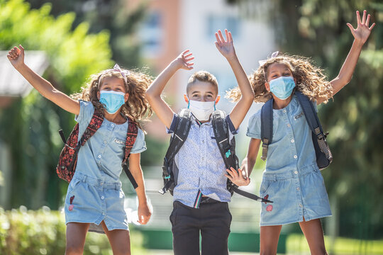 Happy schoolchildren with face masks jump from joy to return to school during the Covid-19 quarantine.