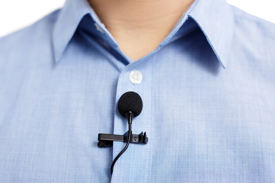 sound recording concept - close up of small lavalier clip-on microphone on blue male shirt