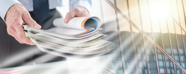 Businessman holding magazines; multiple exposure