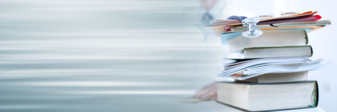 Stethoscope on a stack of medical books; panoramic banner