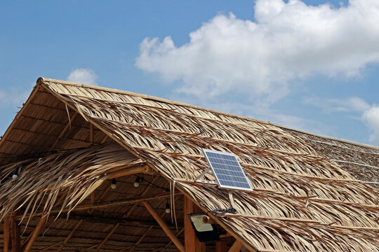 A solar panel on the roof of a thatched hut against blue sky and clouds.