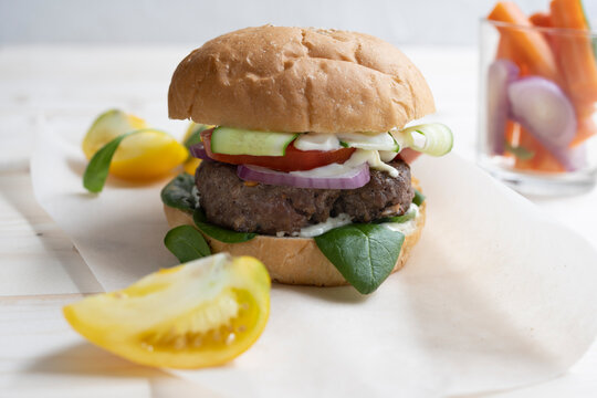 Milanese burger, with tomatoes, lettuce and french fries, in white background